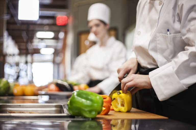 A closeup of the hands of a chef cutting vegetables in a commercial kitchen.
